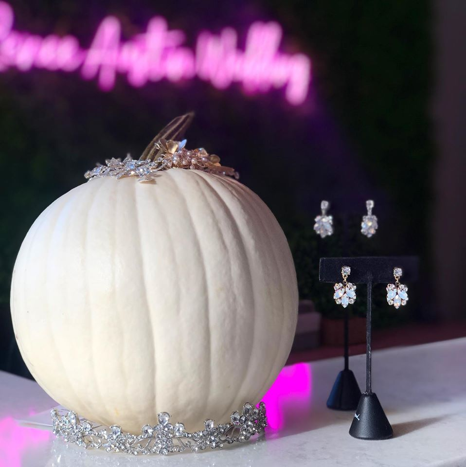 White pumpkin sitting over a tiara and some silver drop earrings next to the pumpkin and some hairpieces on top of the pumpkin