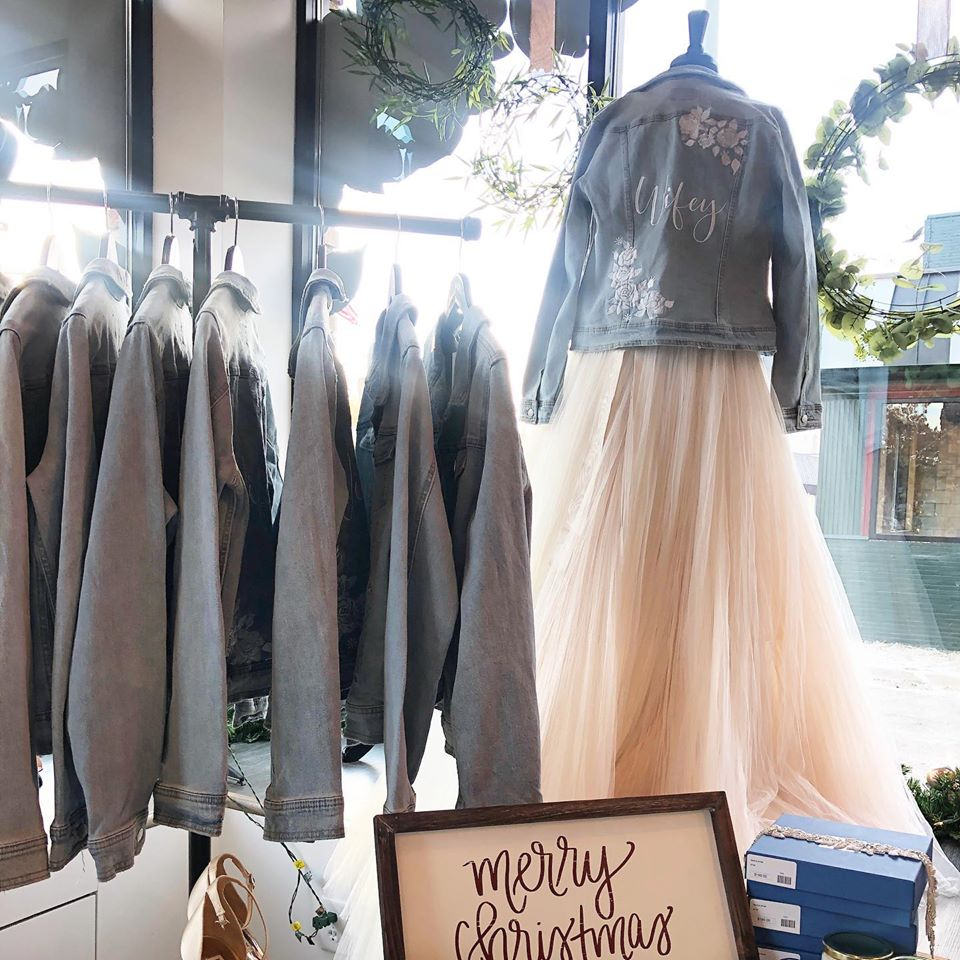 A rack of embroidered jean jackets and one jean jacket on the mannequin over a wedding dress